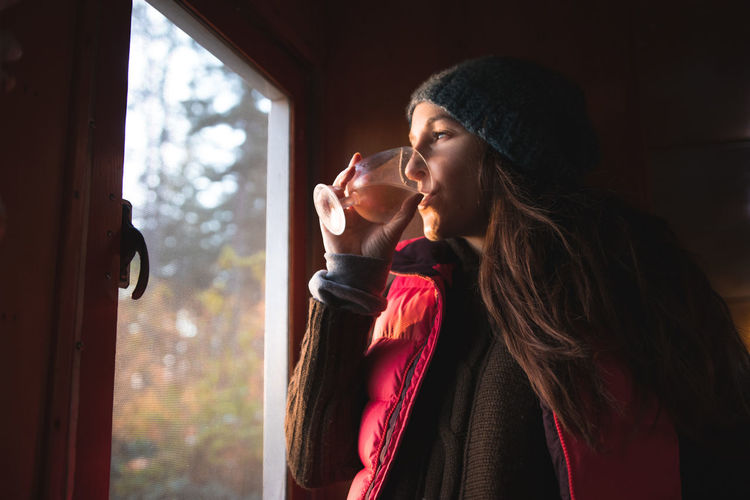 Young woman having drink by window at home