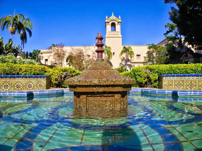 Fountain in swimming pool against clear blue sky