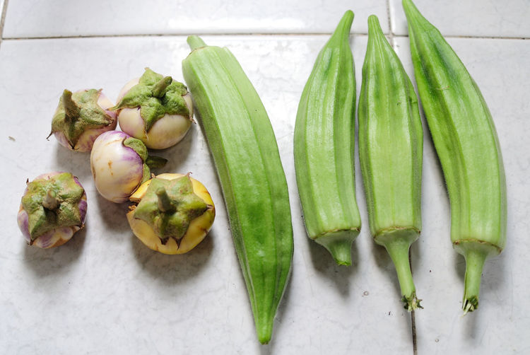 Directly above shot of okras with eggplants on kitchen counter
