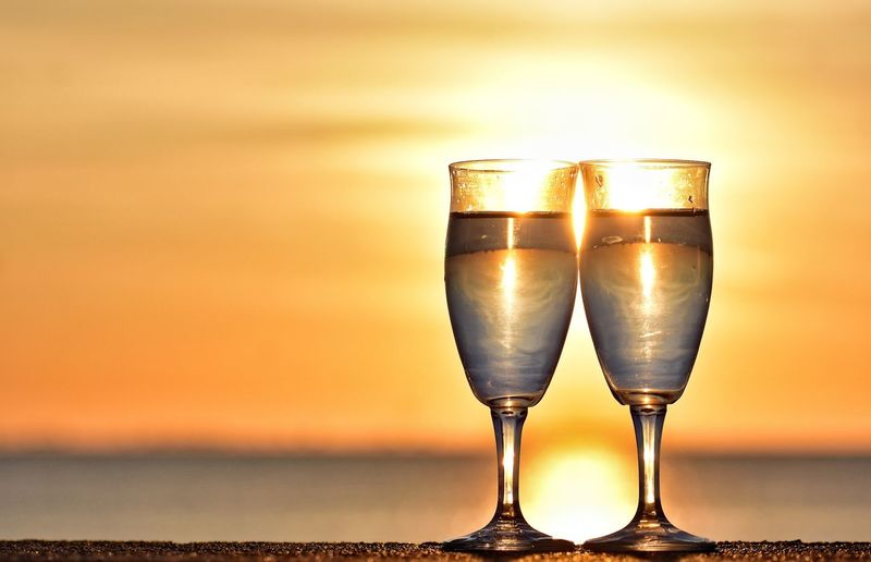 Close-up of wine glass against sunset
