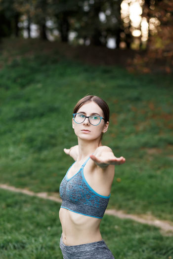 Portrait of young woman wearing sunglasses standing on field