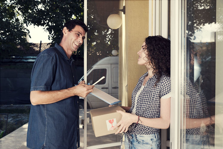 Smiling Delivery Man Talking To Woman Against House