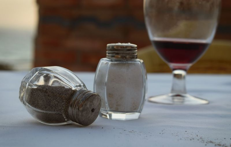 Close-up of salt and pepper shakers with wineglass on table at sidewalk cafe