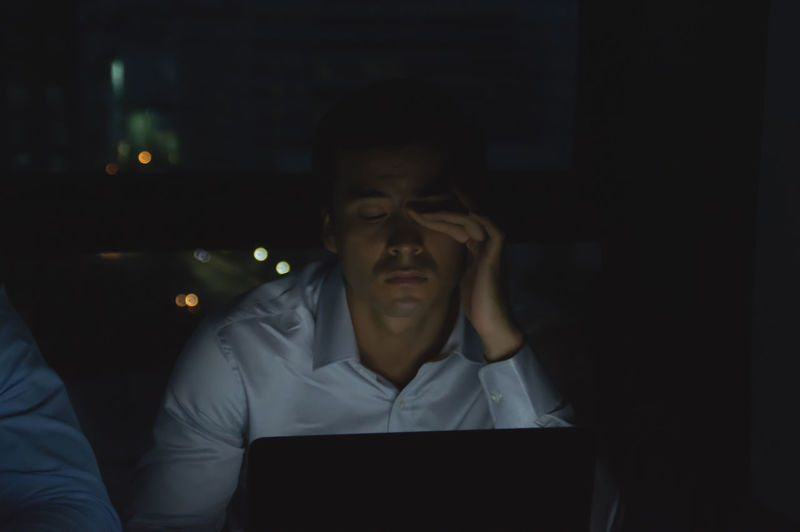 Tired businessman rubbing eyes while working late in office at night