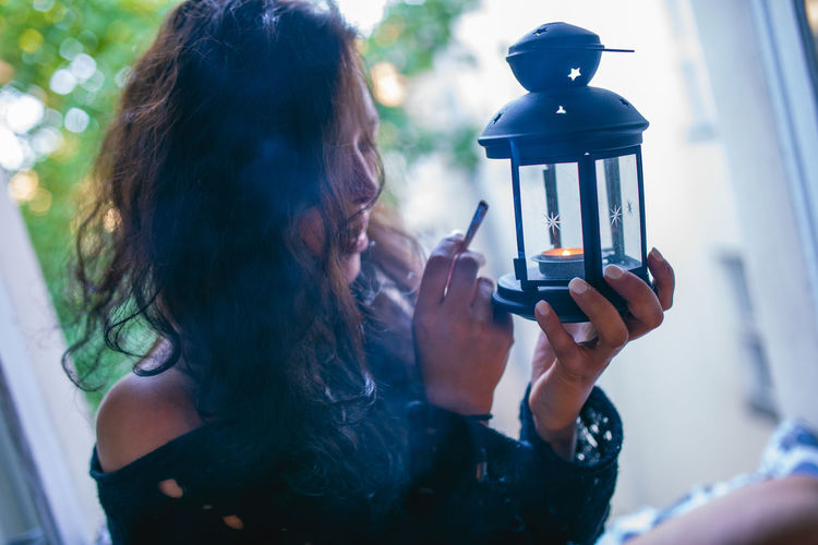 Woman igniting cigarette from lantern at home