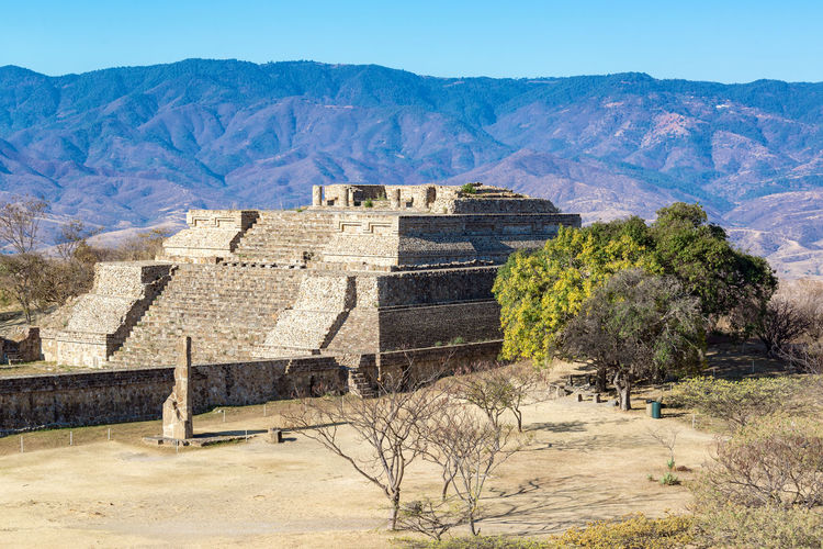 View of a temple in Monte Alban with hills rising in the background in Oaxaca, Mexico Ancient Archeology Architecture Cityscape Hills Mayan Mayan Ruins Mexico Oaxaca Oaxaca México  Pyramid Ruins Temples Travel Civilization Culture Maya Monte Alban Mountain Platform Ruin Stone Stones Temple Tourism