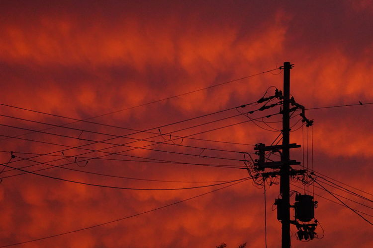 Low angle view of electricity pylon against dramatic sky