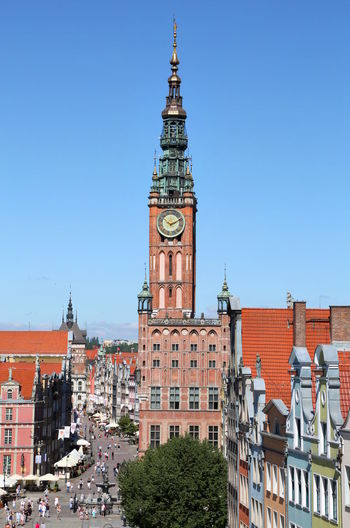 Clock Tower By Buildings Against Clear Blue Sky In City