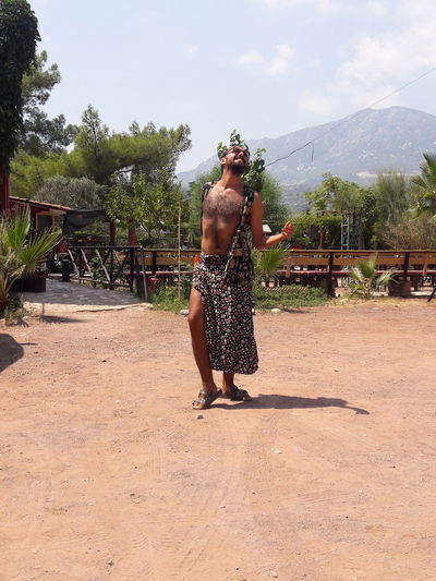 Full length of shirtless man standing on mountain against sky