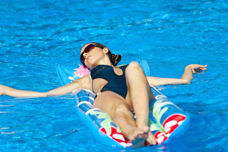 young beautiful woman at the swimming pool Beautiful Woman Beauty Bikini Blue Day Enjoyment Floating On Water Fun Happiness Leisure Activity Lifestyles Lying On Back One Person Outdoors Pool Raft Real People Smiling Summer Swimming Swimming Pool Swimwear Vacations Water Young Adult Young Women