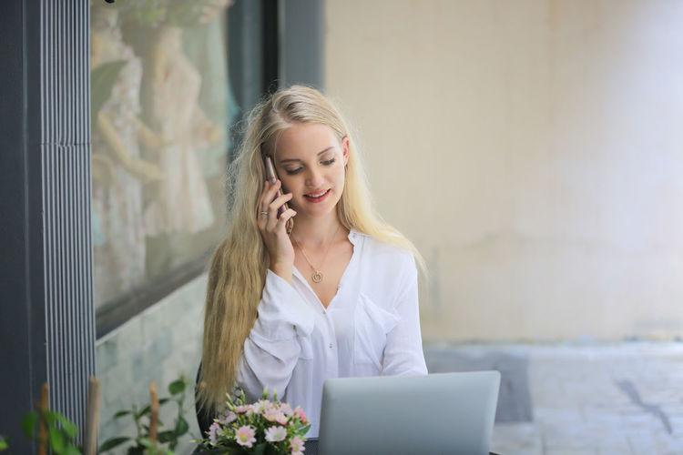 Beautiful young woman using smart phone outdoors