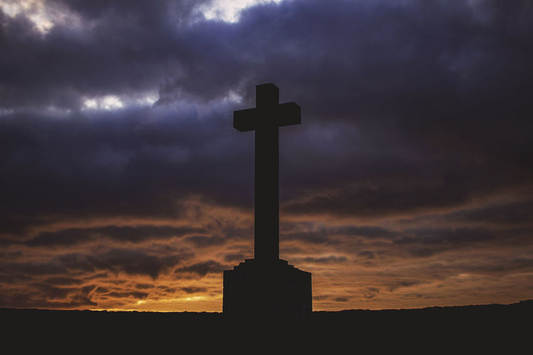 Low angle view of silhouette cross against dramatic sky