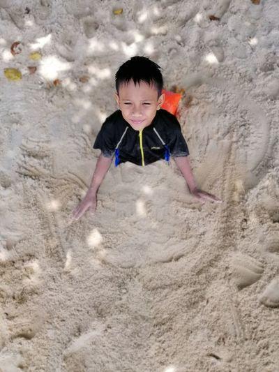 High angle view of boy playing on sand
