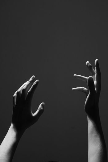 Cropped hands gesturing against gray background