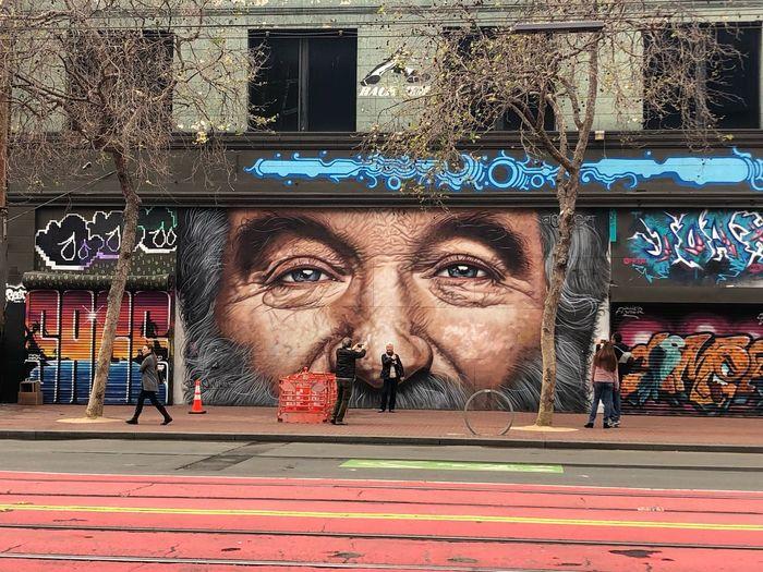 Portrait of man against graffiti wall