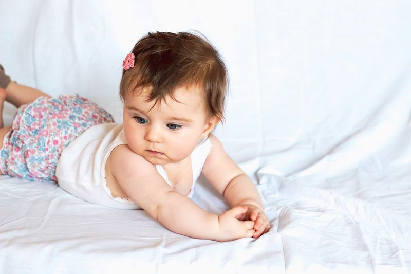 pensive baby girl Pensive Lying On Front Hairclip Toddler  Child Bed Childhood Young Baby Indoors  Lying Down Innocence Cute Real People One Person Bedroom Babyhood Front View Sheet