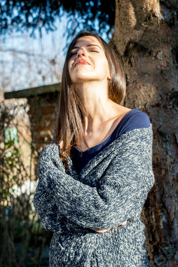 Young woman with closed eyes standing against tree during sunny day