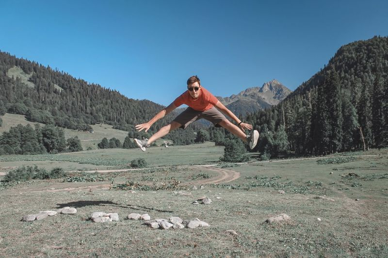 Portrait of young man in mid-air by land against sky