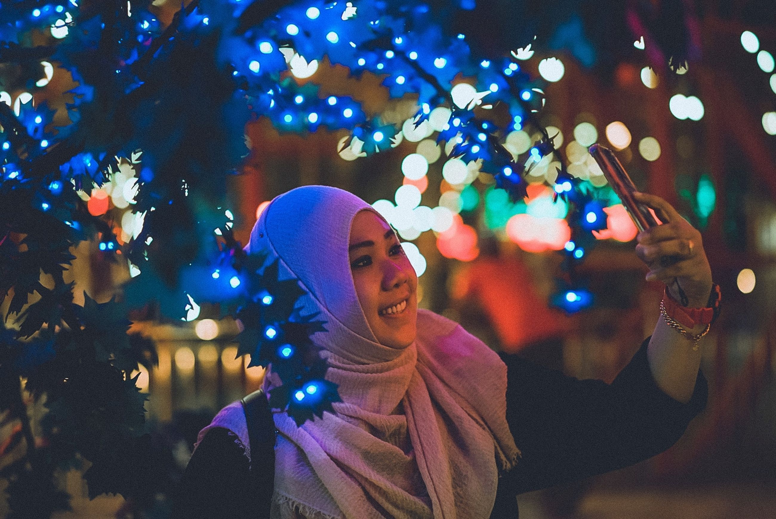 illuminated, one person, night, real people, smiling, happiness, portrait, lifestyles, leisure activity, front view, tree, celebration, young adult, emotion, focus on foreground, clothing, decoration, young men, christmas, light, warm clothing