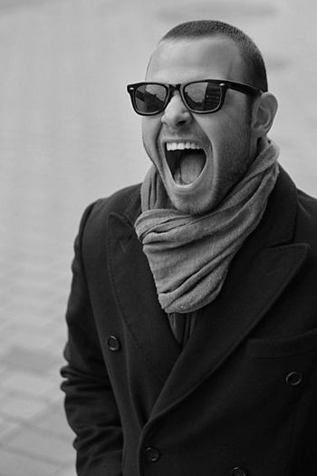 Frustrated man screaming while wearing sunglasses