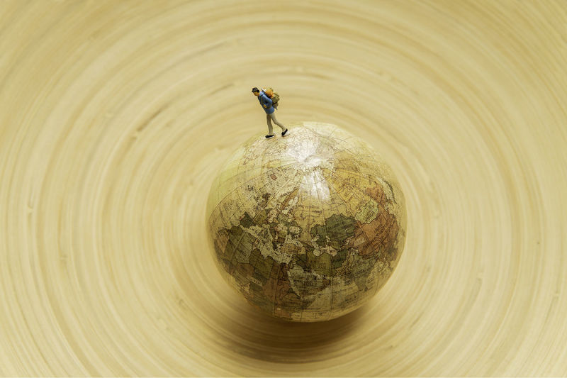 High angle view of figurine over globe on wooden table
