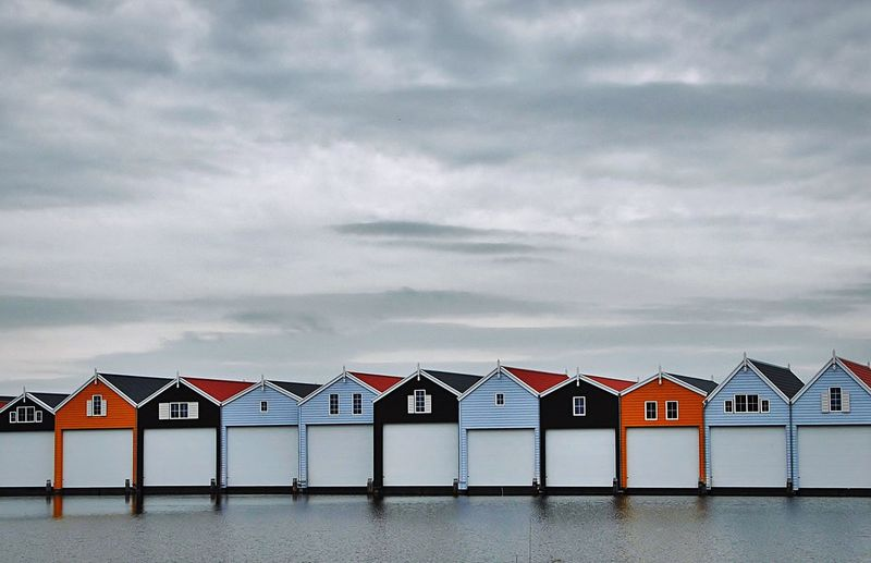 Beach huts in front of sea against cloudy sky