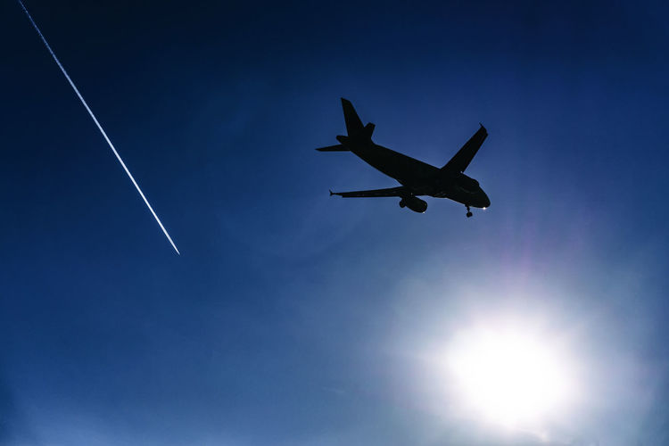 Silhouette of Aircraft Landing Against Low Afternoon Sun with Contrail Berlin Germany 🇩🇪 Deutschland Horizontal Color Image Outdoors No People Flying Air Vehicle Airplane Transportation Sunlight Plane Public Transportation Vapor Trail Contrail Condensation Trail Silhouette Mid-air Mode Of Transportation on the move Aircraft Low Angle View Sky Blue Clear Sky