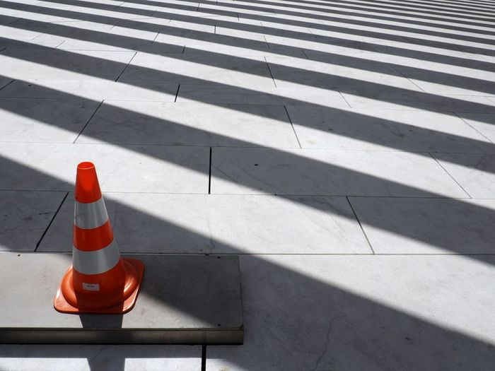 High angle view of traffic cone on footpath during sunny day