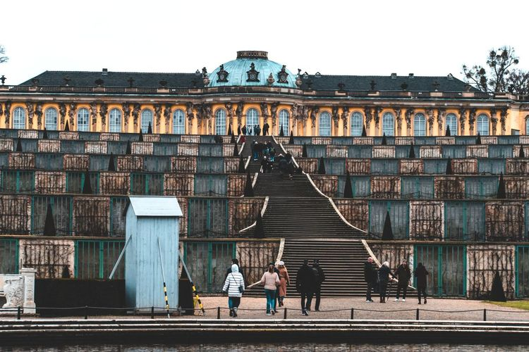 People walking on building against sky in city