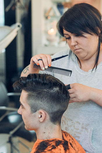 Woman cutting man hair in salon