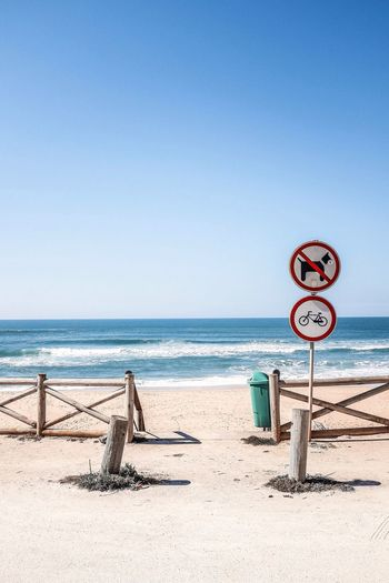 Scenic view of beach entrance and sign post against blue sky
