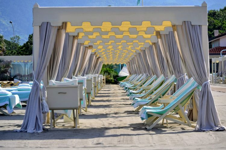 Empty deck chairs arranged at beach