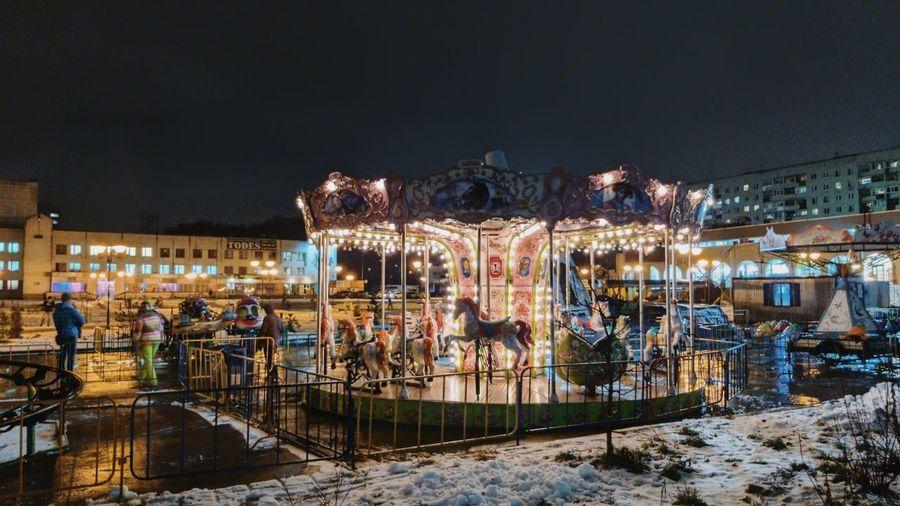 Illuminated ferris wheel in city at night during winter