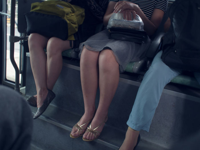 Low section of women sitting on escalator
