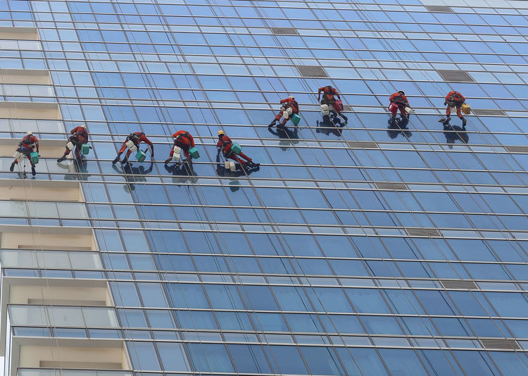 Low angle view of men working against sky