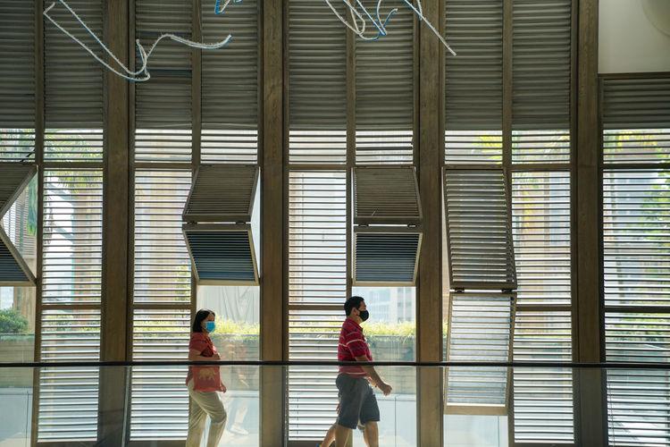 Side view of people walking in corridor of building