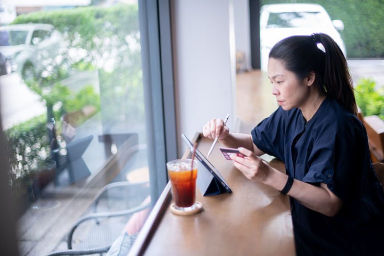 Young woman using smart phone in cafe