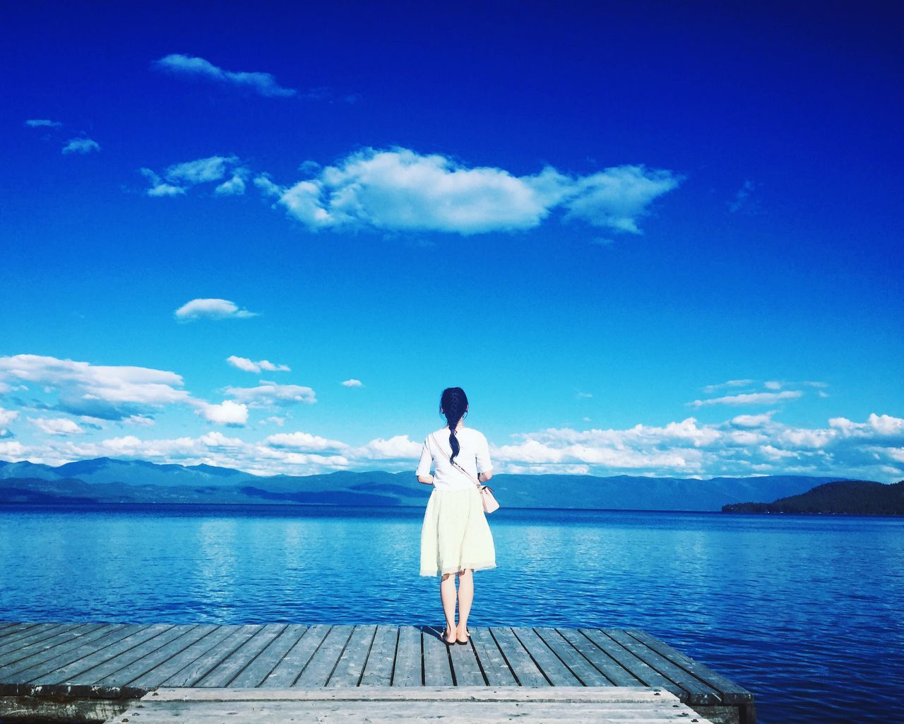 cloud - sky, sky, one person, rear view, water, lake, blue, tranquil scene, nature, full length, scenics, beauty in nature, standing, day, mountain, leisure activity, tranquility, women, outdoors, young adult, real people, one young woman only, adult, people