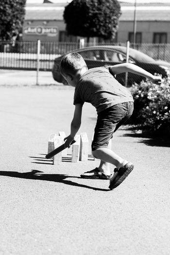 Full length of boy skateboarding on street