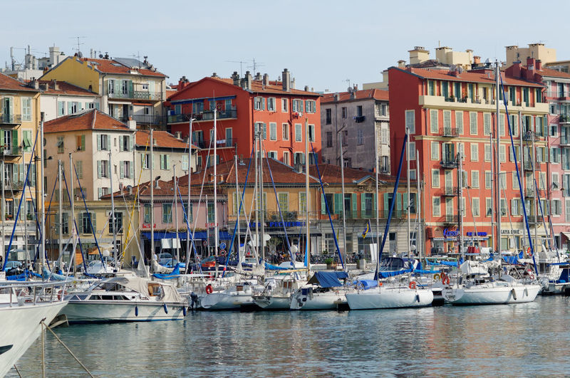 Sailboats moored on sea against buildings in city