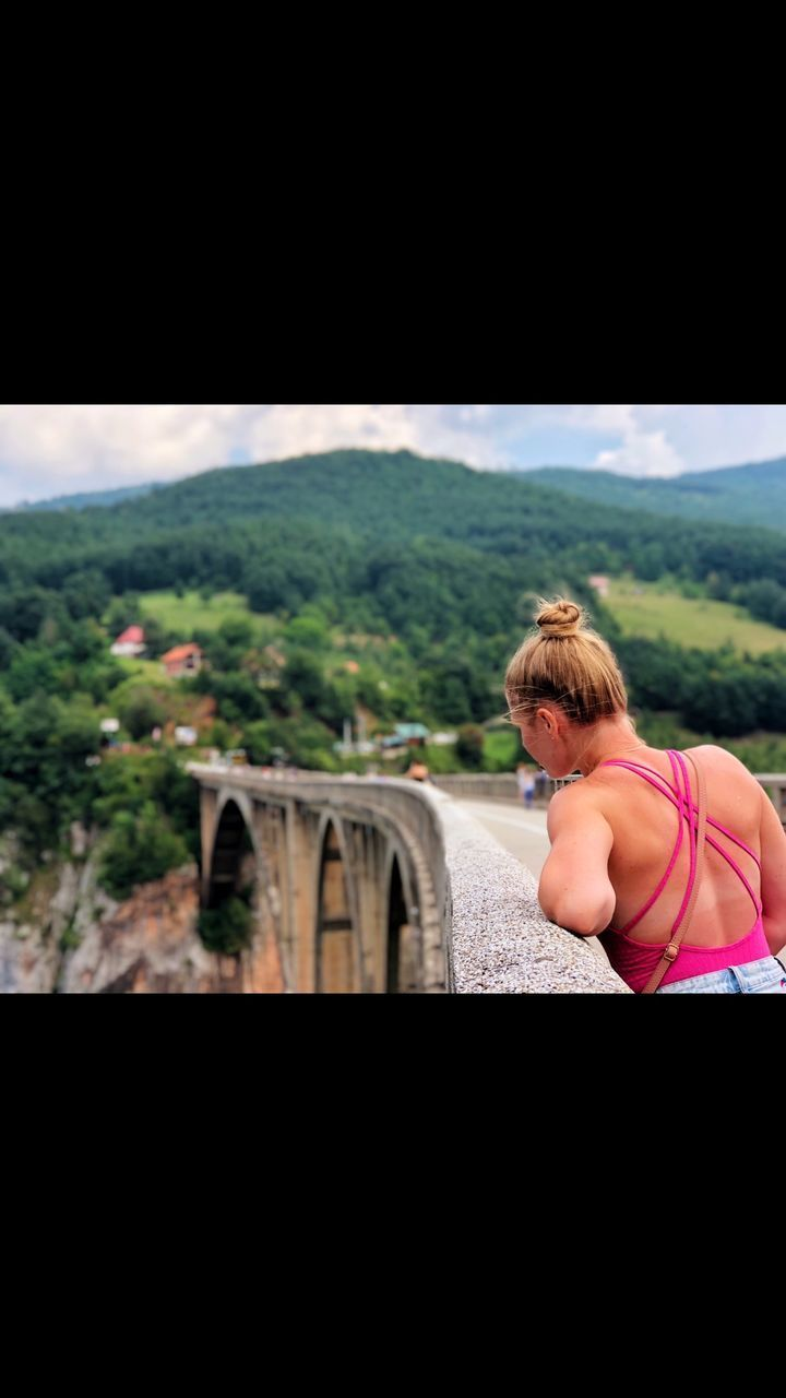 REAR VIEW OF WOMAN LOOKING AT BRIDGE OVER RIVER