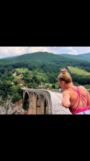 Rear view of woman looking at bridge against sky