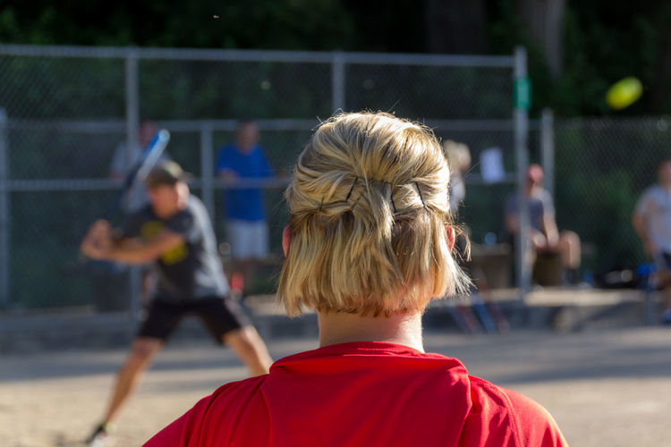 Rear View Of Girl Looking At Men Playing Baseball On Playing Field