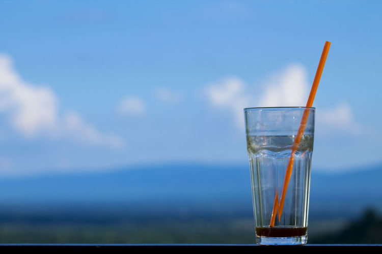 Close-up of drinking glass on table against blue sky