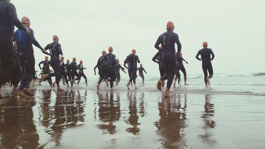Divers Running At Beach