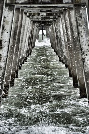 under the pier Water Architecture No People Built Structure Day Outdoors Nature In A Row The Way Forward Waterfront Direction Connection Architectural Column Sea Motion Pier Diminishing Perspective Underneath Bridge Flowing Water