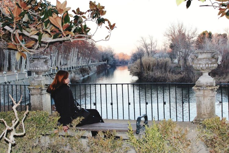 Side view of woman sitting on bench by lake