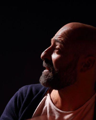 Close-Up Of Bald Man Against Black Background
