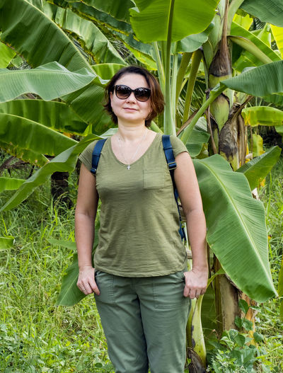 Portrait of woman wearing sunglasses while standing against banana tree
