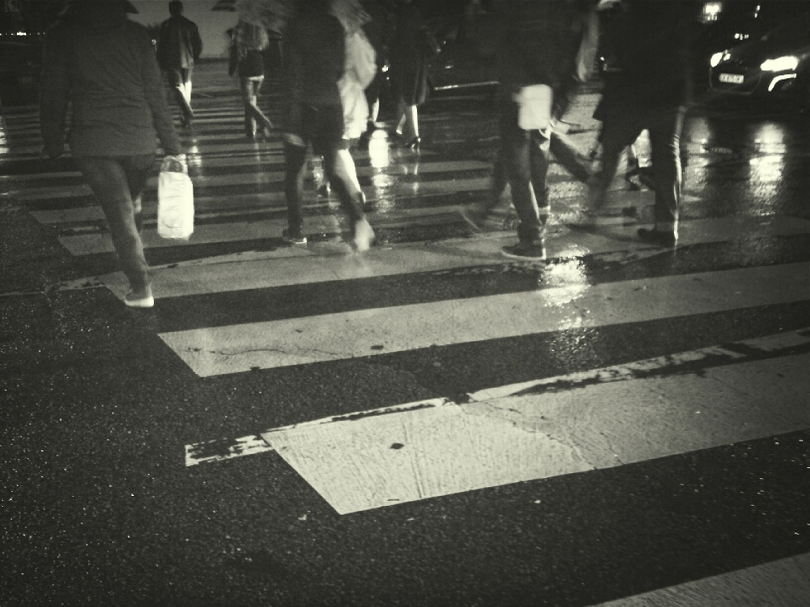 men, walking, lifestyles, street, low section, person, city life, leisure activity, zebra crossing, road marking, shadow, on the move, night, road, high angle view, standing